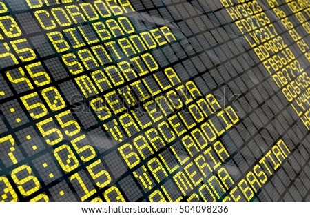 Close-up of an airport departure board to Spanish cities destinations, with environment reflection.Part of a series.
