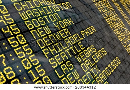 Close-up of an airport departure board to usa cities destinations, with environment reflection.Part of a series.