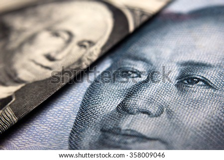 Close-up of an American dollar bill (showing George Washington) and a Chinese yuan banknote (Mao Zedong) - stock photo