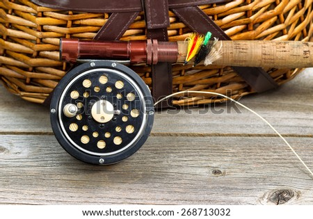 Close up of an antique fly fishing reel, rod, and artificial flies in front of creel with rustic wood underneath. Layout in horizontal format. - stock photo