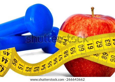 Close-up of an apple with a measuring tape around on white background - stock photo