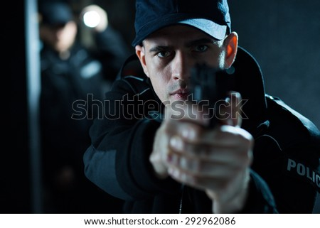 Close up of an armed policeman pointing pistol - stock photo