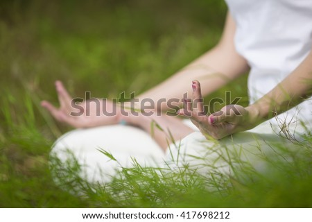 Close up of an Asian woman's hands practicing yoga in a garden. healthy lifestyle and relaxation - stock photo