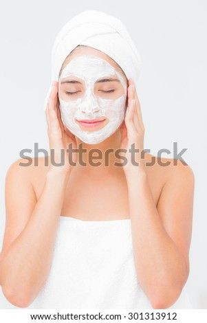 Close-up of an attractive woman having white cream on her face at spa center
