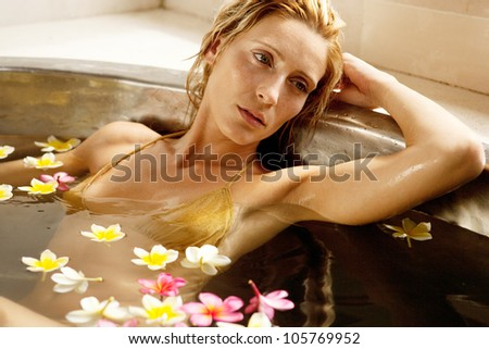 Close up of an attractive woman in a bath of flowers, relaxing.