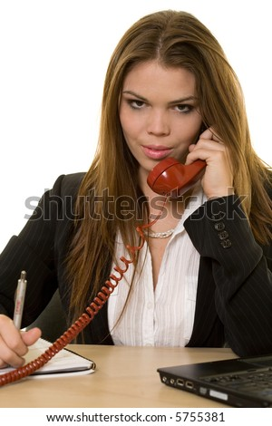 Close up of an attractive young brunette woman in business suit talking on an old style red phone while sitting at a desk and writing in a calendar - stock photo