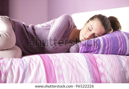 Close-up of an attractive young female sleeping in bed at home - stock photo