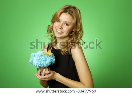 Close-up of an attractive young woman holding a gift bouquet of blue chrysanthemums. Bouquet romantic letter
