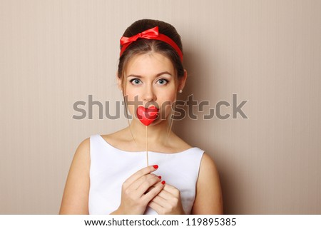 Close up of an attractive young woman holding a red heart.