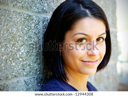 Close-up of an attractive young woman leaning against a concrete wall. Horizontally framed shot. - stock photo
