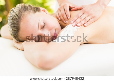 Close-up of an attractive young woman receiving shoulder massage at spa center