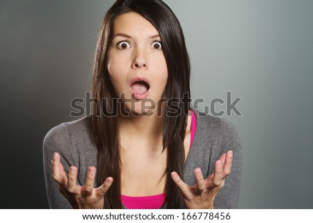 Close up of an attractive young woman with a horrified expression clenching her hands in frustration and desperation as she stares open-mouthed at the camera