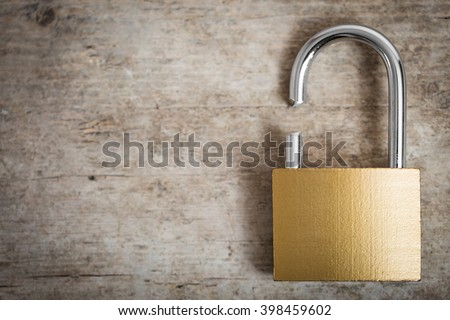 close-up of an broken padlock on a wooden table, concept security and safety