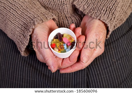 Close up of an elderly hand holding pills. - stock photo