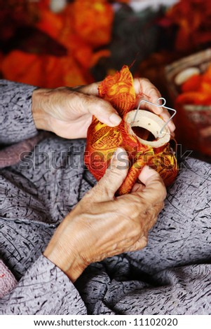 Close-up of an elderly woman making traditional silk lanterns from Vietnam - travel and tourism.