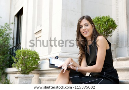 Close up of an elegant businesswoman sitting on a classic buildings steps taking notes in her agenda, smiling. - stock photo