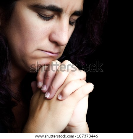 Close-up  of an hispanic woman praying with a sad face isolated on black