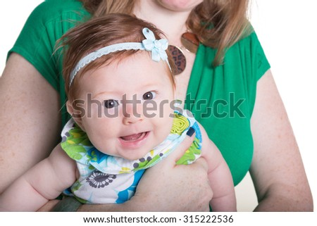 Close up of an infant being held by her mother - stock photo
