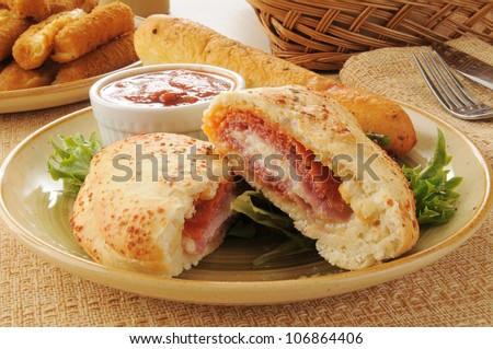 Close up of an Italian Calzone with bread and mozzarella cheese sticks - stock photo