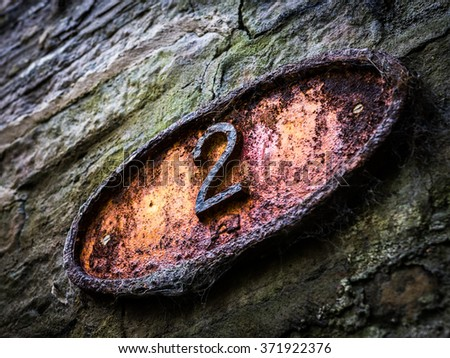 Close up of an old and rusty yet still vibrant bridge number.