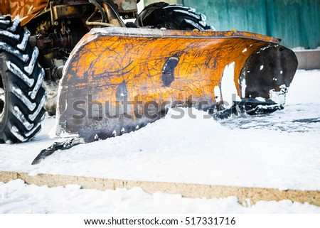 Close-up of an old excavator removing snow from the street, selective focus