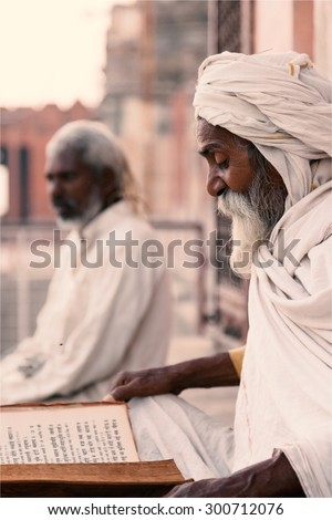 Close up of an old indian sadhu (saint) sitting and reading sacred texts near the temple. Varanasi (India) on 23 Nov 2014.