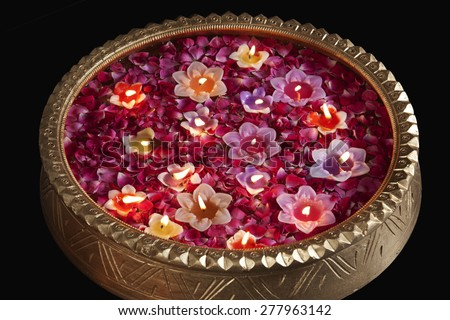 Close-up of an urn with floating diyas - stock photo