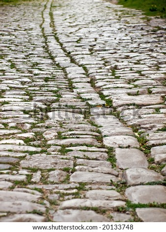 Close up of ancient road with smooth stone tiles. - stock photo