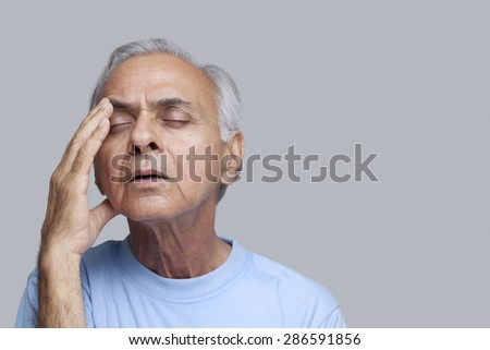 Close-up of and elderly man suffering from headache with eyes closed
