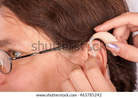 Close-up of and inserting a hearing aid in the ear