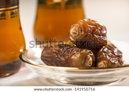 Close up of arabic dates and tea cups - stock photo
