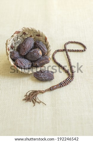 Close up of arabic dates, lantern and rosary against jute fabric background - stock photo