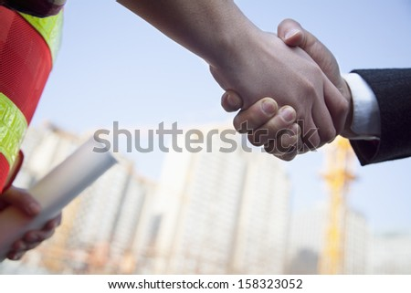 Close up of architect and building contractor shaking hands - stock photo