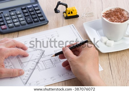 Close-up of architect hands working on a blueprint. Calculator, cup of coffee and miniature extractor in the background. Blueprint was created by photographer. - stock photo