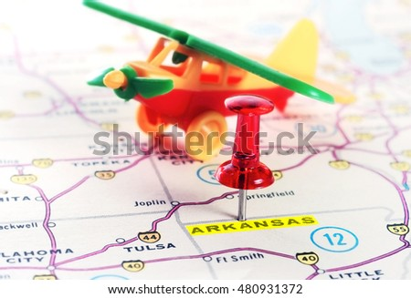 Close up of  Arkansas  USA map with red pin and airplane  toy - Travel concept