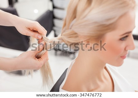 Close up of arms of hairstylist making pretty plait for a woman. The young girl is sitting and smiling - stock photo