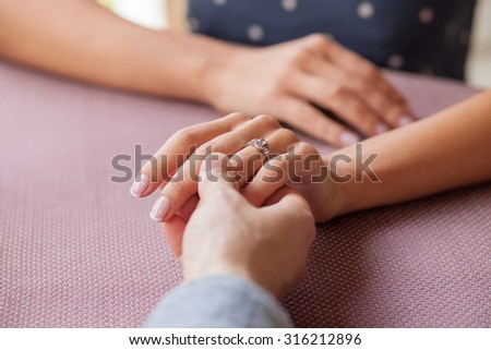 Close up of arms of loving couple sitting at the table in cafe. They are holding hands with love. There is the engagement ring on female finger - stock photo