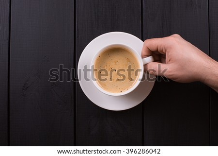 Close up of arms of successful business having a business meeting with his client in cafe. The man in suit is drinking coffee - stock photo