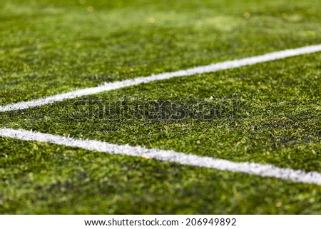Close-up of artificial green soccer turf on a sunny day. - stock photo