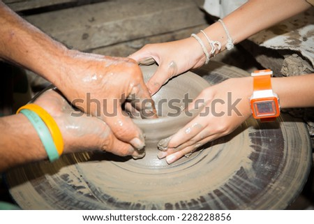 close up of Asian child hands and potter hand craft is training - stock photo