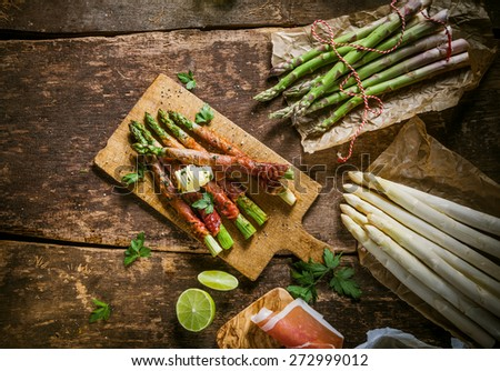 Close Up of Asparagus Wrapped in Bacon with Curl of Butter on Rustic Wooded Board Surrounded by Raw Ingredients - stock photo