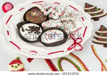 Close up of assorted Christmas cookies on a white plate decorated with a red ribbon. - stock photo