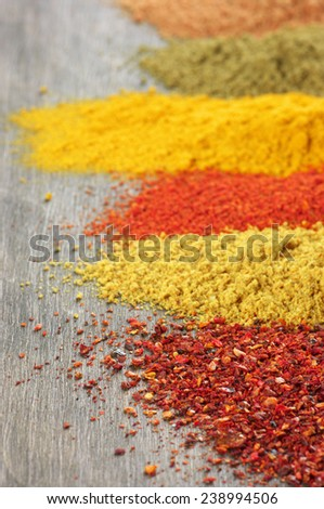Close-up of assorted loose powder spices on wood. Shalow DOF, focus on foreground. - stock photo