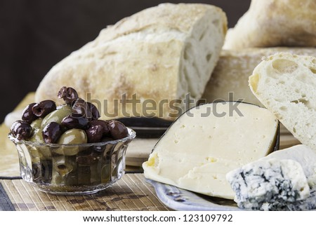 Close up of assorted olives with rustic breads and cheese - stock photo
