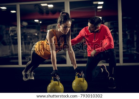 Close up of attractive strong motivated young fitness woman in sportswear doing push ups on the kettlebells while her personal trainer crouching next to her and supporting.