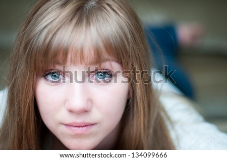 Close up of attractive teen girl lying down on couch - stock photo