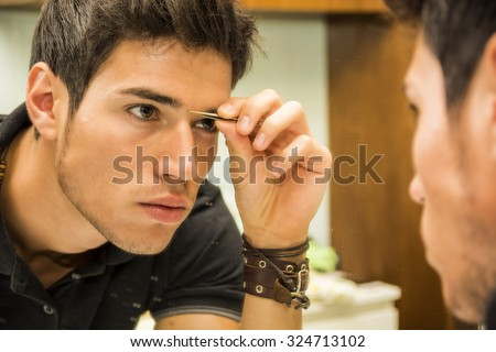 Close Up of Attractive Young Man with Dark Hair Grooming Himself - Plucking Stray Eyebrow Hairs with Tweezers While Looking into Bathroom Mirror - stock photo