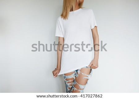 Close up of attractive young woman in blank white T-shirt for your text message or advertising content. Cropped portrait of cute Caucasian teenage blonde girl posing against white concrete wall.  - stock photo