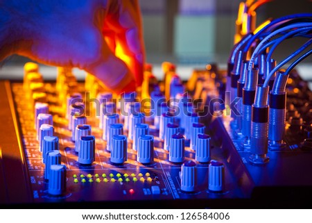 Close-up of audio mixing desk. Motion blurred hand on distant controls. Selective focus on foreground LEDs. - stock photo
