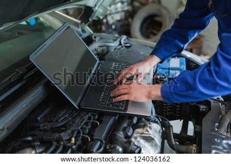 Close-up of auto mechanic using laptop - stock photo